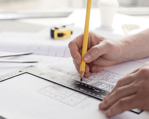 architect home design man drawing up home plans with pencil and ruler